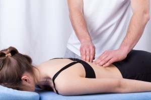 Physiotherapist touching tense muscle of the back